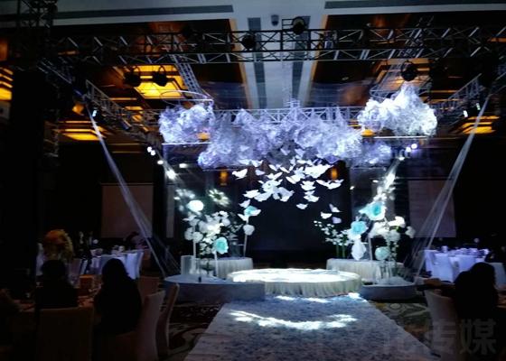 第一种:浪漫温馨风格的,这种风格的舞台布置主要以白色、紫色、粉色为主要基色,给人一种年轻时尚、浪漫奢华的感觉,舞台背景用LED大屏加上试先制作好的视频作背景,再加上大量灯光秀,全场整个色系围绕主色调,并加上大量鲜花陪衬,整个舞台及会场布置可以说非常的浪漫温馨。